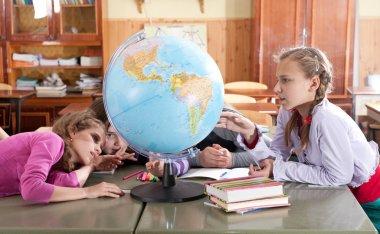 Schoolchildren exploring globe in classroom