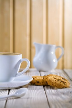 Coffee in the cup and cookie, milk bowl on white old table