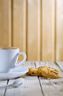 Coffee cup and cookies on old white table
