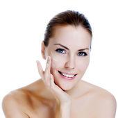 Fotografie Happy smiling beautiful woman applying moisturizer cream on the face