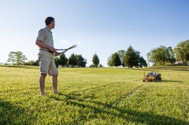 Senior man cutting grass with shears