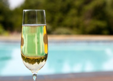 Flute of cold champagne by side of pool