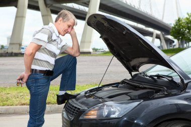 Confused mature driver standing front of car with opened engine compartment hood