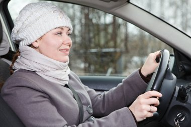 Woman in winter clothes driving a car