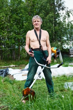 Mature man a lawn-mower with chopper trimer mowing grass.