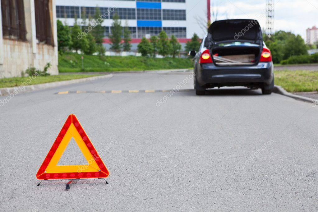Triangle warning sign on road foreground and broken car with