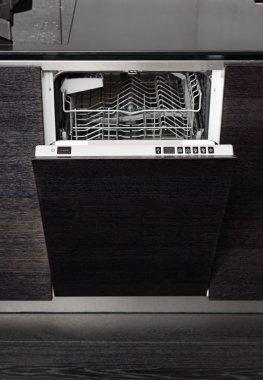 Open dish washer machine on black hardwood kitchen
