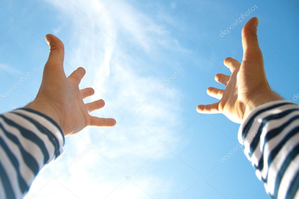 Hands in air across blue sky