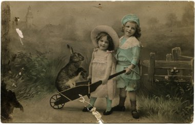 Two girls with a rabbit in a wheelbarrow