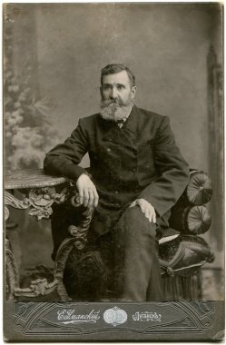 RUSSIA - CIRCA the end of 19 - early 20 century: An antique photo shows man in a business suit with a mustache and beard, sitting in a chair at the table, Lugansk, Russian Empire, now Ukraine Russian text: Umanskiy (photographer), Lugansk
