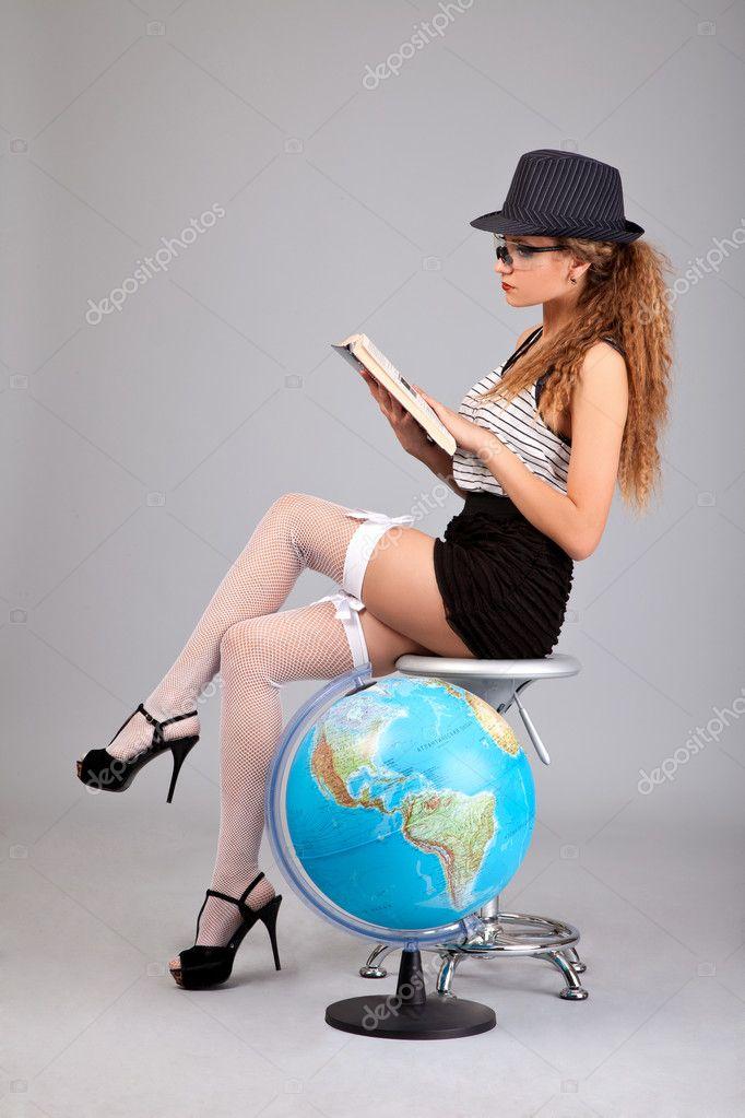 Sexy teacher holding a book on grey