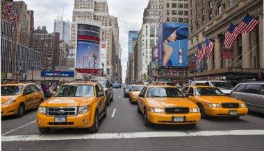 NEW YORK - MAY 28: Group of yellow taxi cabs rush tourists aroun