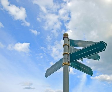 Blank old directional road sign post over blue sky.
