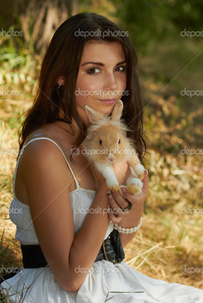 Beautiful young girl holding a bunny