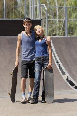 Teen skaters with boards in skatepark
