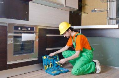 Repairman assembling the furniture at kitchen