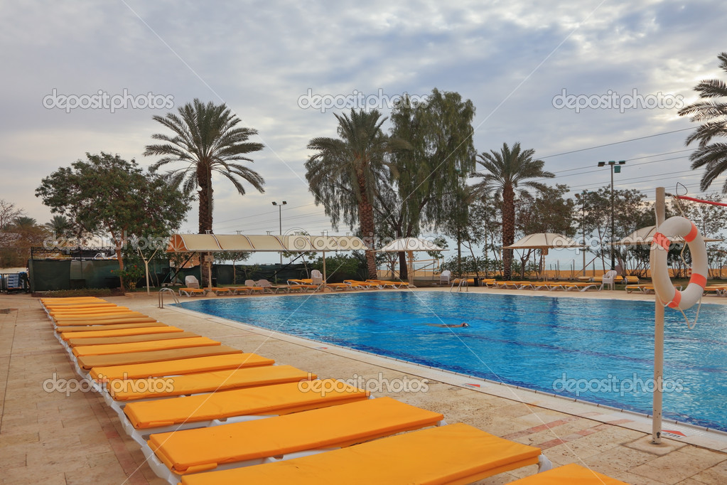 The swimming pool and beach loungers