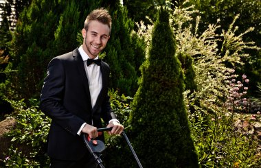 Glamour gardener mows a grass with lawn-mower