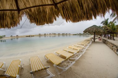 Straw umbrella and chairs on the beach of Roatan, Honduras