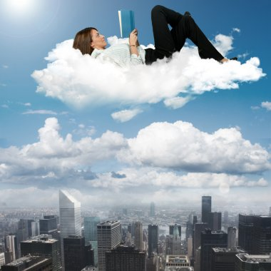 Businesswoman reading book on a cloud