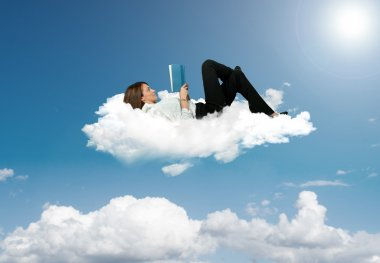 Businesswoman reading a book in a cloud