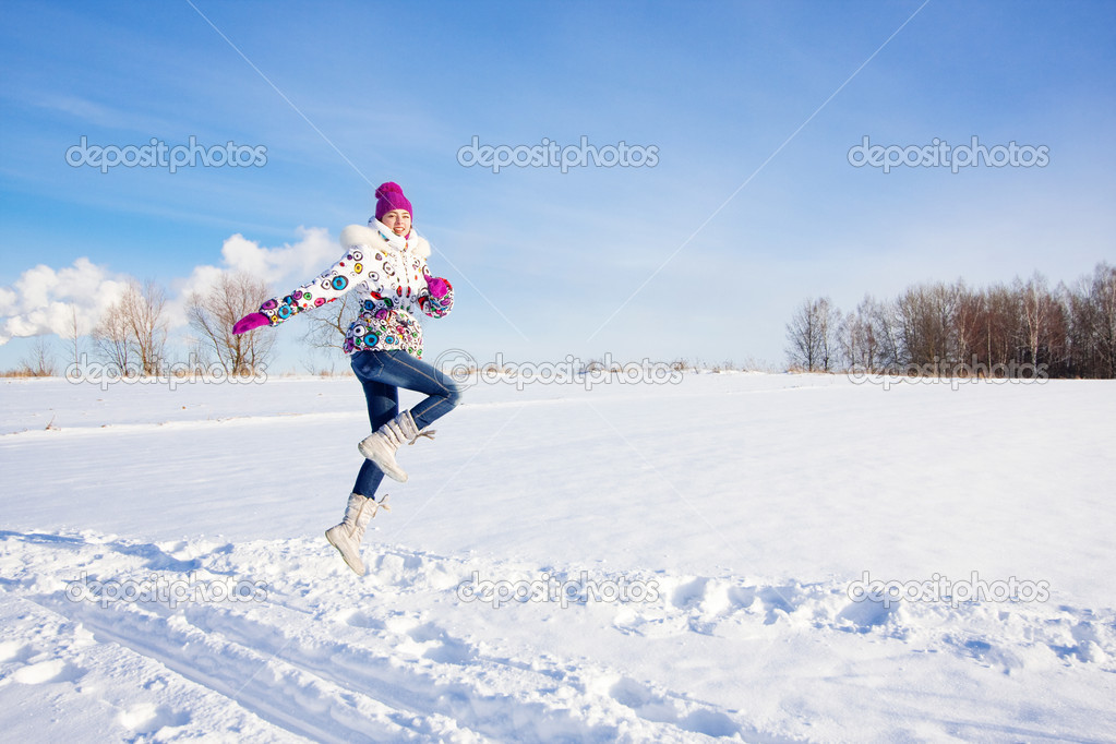 Outdoor winter portrait of beautiful smiling young girl