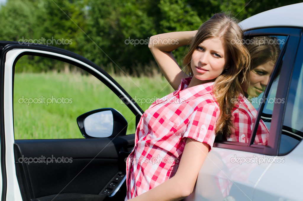 The beautiful girl stands near to white car