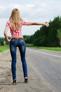 The girl in jeans stops the car on road