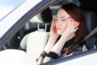 Woman with headache in a car
