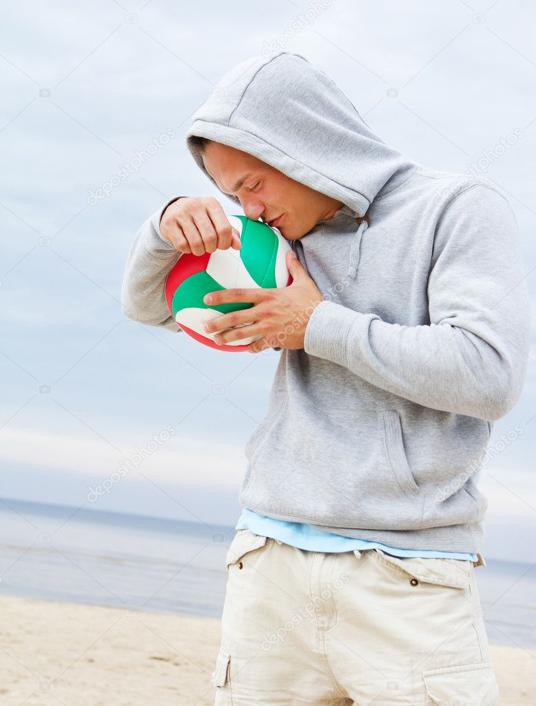 Portrait of man posing on the beach with ball