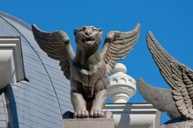 Sculptures of lions on the roof of building on a background blue