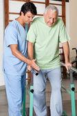 terapeut pomáhá starší muž chodit s podporou pruhů