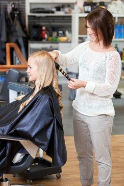 Stylist Curling Womans Hair