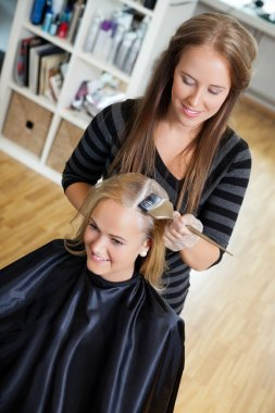 Beautician Applying Hair Colour To Woman