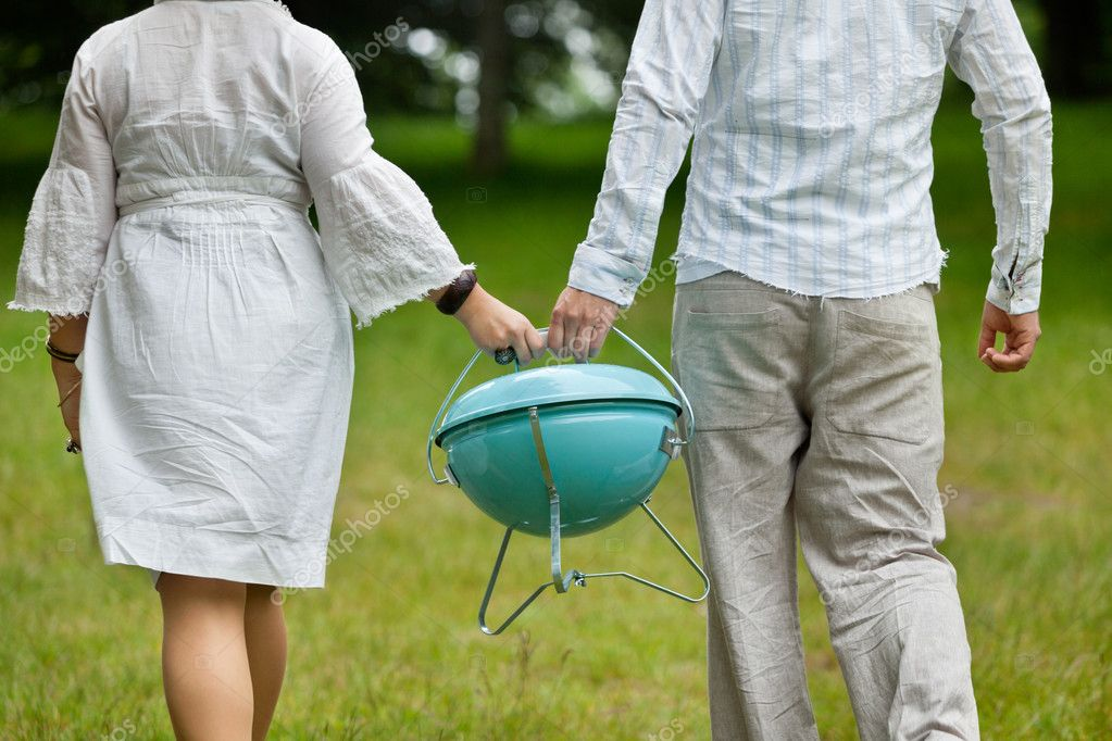 Couple Walking With Portable Barbeque