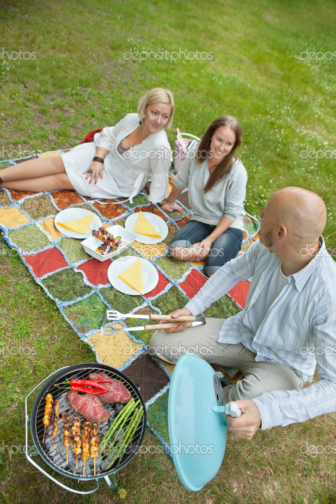 Friends Eating Food At An Outdoor Picnic