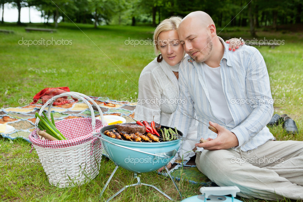 Mature Couple Cooking On An Outdoor Picnic