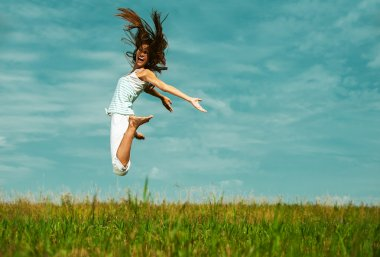Attractive woman jumping in sky