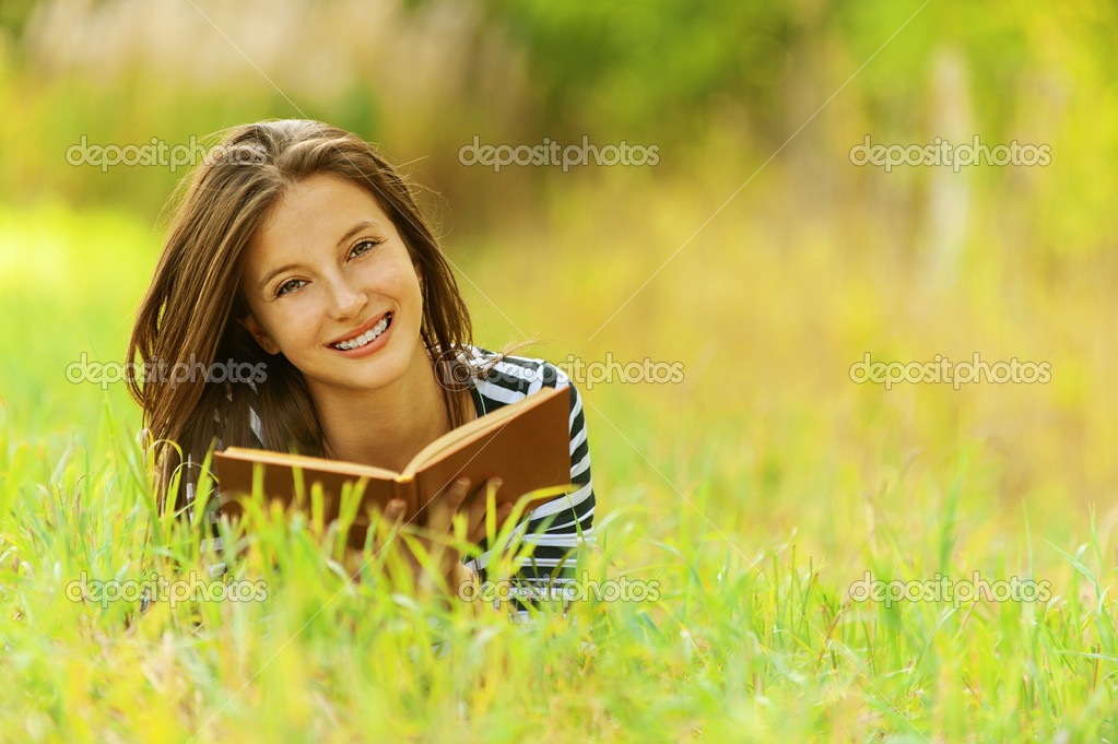 Smiling woman lying on grass reading book