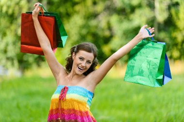 Woman happily holds up with shopping bags