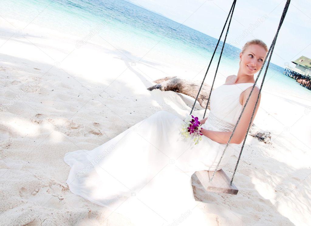 Beautiful bride swinging on tropical sea side background