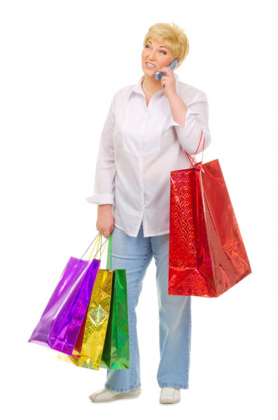 Senior woman with mobile phone and bags