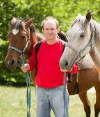 schöner lächelnder Mann mit Pferd im Wald
