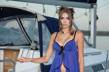 The charming beauty poses at the yacht