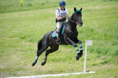 Rider eventer on horse negotiating cross-country fence open ditch