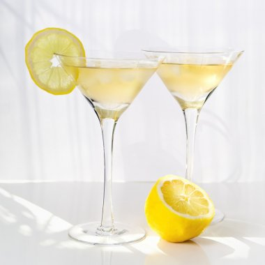 Martini alcohol cocktail with yellow lemon on white