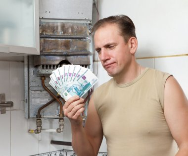 The sad man counts money for repair of a gas water heater