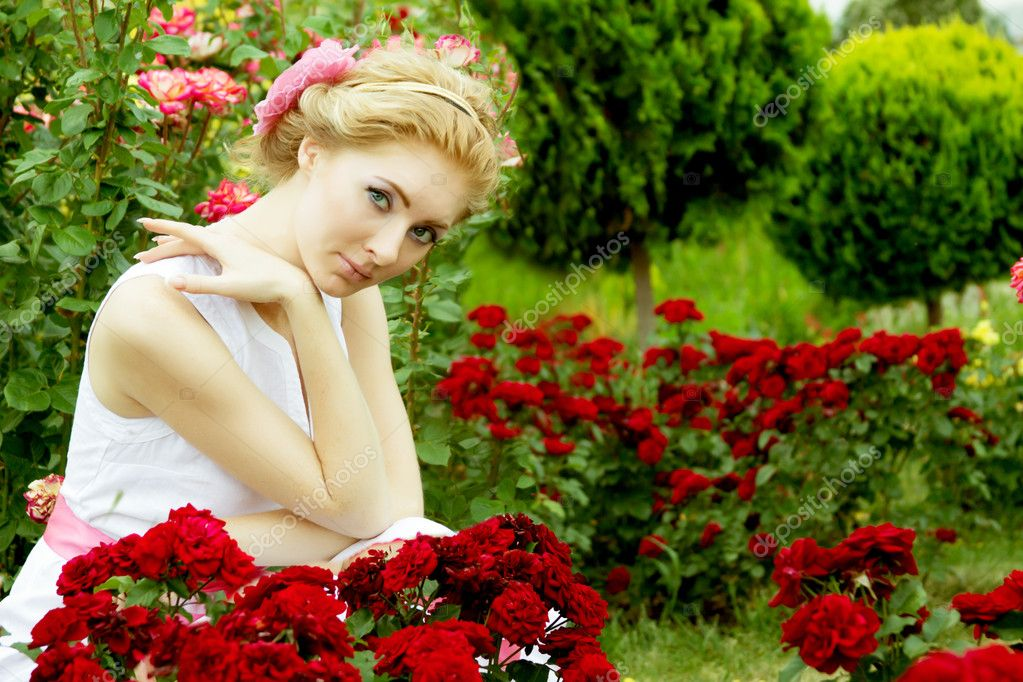 Woman in white dress among rose garden