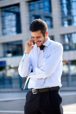 Smiling businessman talking on a mobile phone.