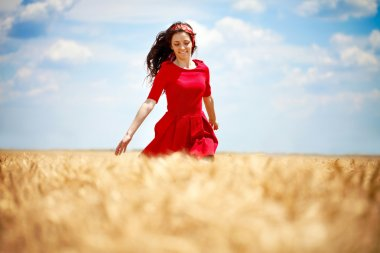 Romantic woman running across field